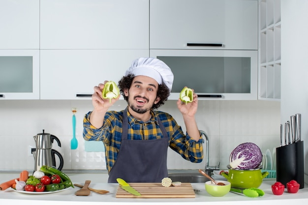 Front view of smiling male chef with fresh vegetables and cooking with kitchen tools and showing cut green peppers in the white kitchen