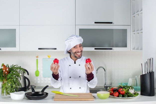 Front view smiling male cook in uniform holding salt shakers in kitchen