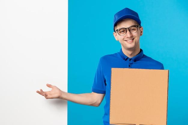 Vista frontale del corriere maschio sorridente in uniforme blu con pizza sul blu