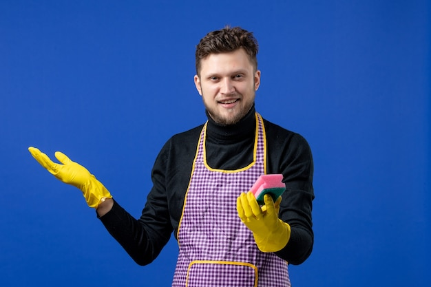 Front view of smiling male housekeeper holding up sponge on blue wall