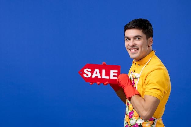 Vista frontale della governante maschio sorridente in maglietta gialla che tiene il segno di vendita sul muro isolato blu