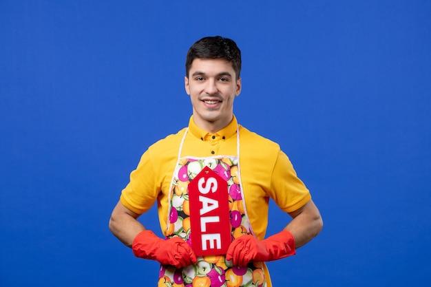 Vista frontale della governante maschio sorridente in maglietta gialla che tiene il segno di vendita sulla parete blu