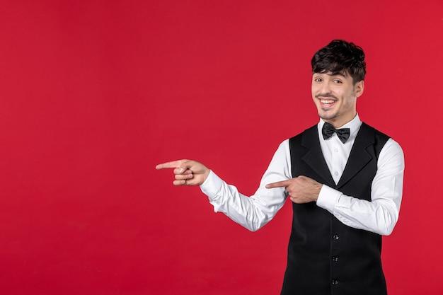 Vista frontale del cameriere maschio sorridente in uniforme con papillon sul collo e puntando qualcosa sul lato destro sulla parete rossa