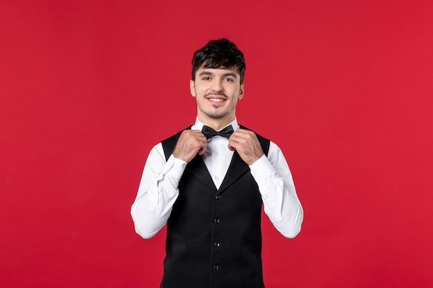 Vista frontale del cameriere maschio sorridente in uniforme con papillon sul collo sulla parete rossa