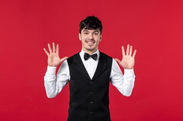 Vista frontale del cameriere maschio sorridente in uniforme con papillon sul collo e mostrando dieci sulla parete rossa