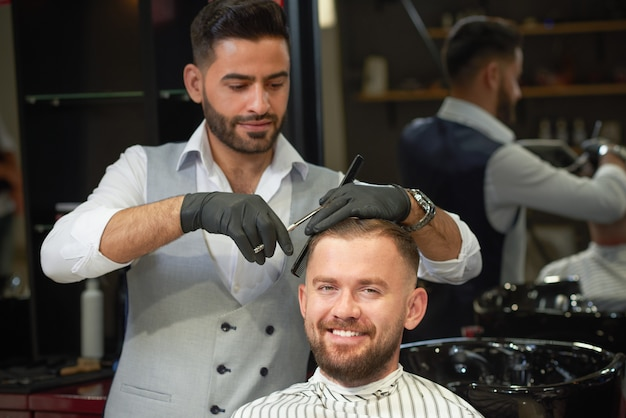 Front view of smiling man getting hairstyle in barbershop