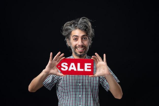 Vista frontale dell'uomo sorridente che tiene il segno di vendita sulla parete scura