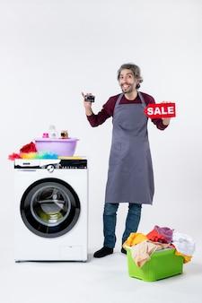 Вид спереди улыбающийся мужчина, держащий открытку и знак продажи, стоящий возле корзины для белья стиральной машины на белой стене