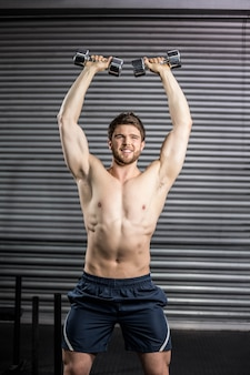 Front view of smiling man lifting weight at gym