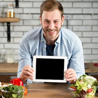 Front view of smiling man showing blank screen digital tablet on kitchen counter