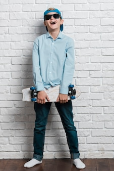 Front view of smiling modern boy with skateboard