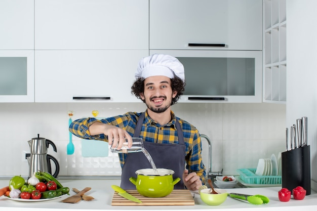 Front view of smiling and positive chef with fresh vegetables adding water into pot in the white kitchen