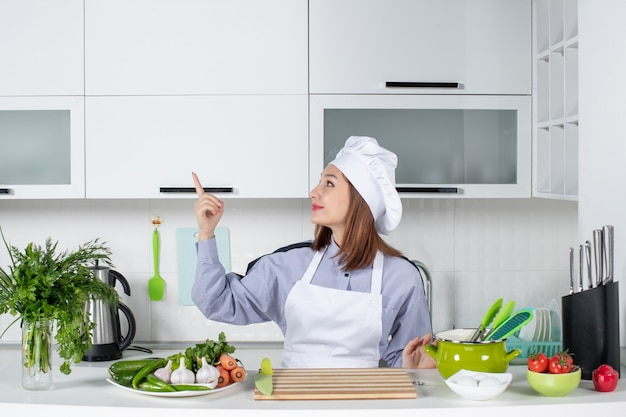Vista frontale dello chef femminile positivo sorridente e verdure fresche che puntano verso l'alto sul lato destro nella cucina bianca