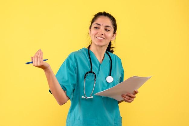 Vista frontale sorridente medico piuttosto femminile che chiama qualcuno in possesso di documenti su sfondo giallo