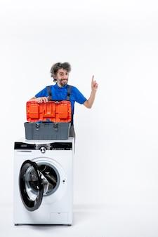 Vista frontale del riparatore sorridente che apre la borsa degli strumenti dietro la lavatrice sul muro bianco isolato