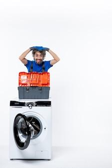 Vista frontale del riparatore sorridente che mette la lavatrice della borsa degli attrezzi sulla parete bianca