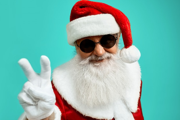 Front view of smiling santa claus with long white beard showing peace with two fingers up. funny senior stylish man in sunglasses posing