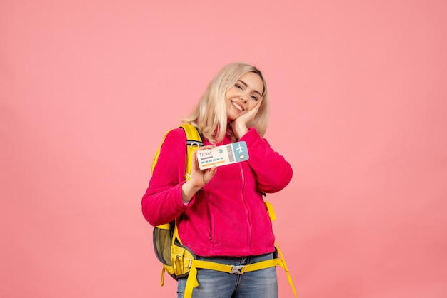 Вид спереди улыбающаяся женщина-путешественница в повседневной одежде в рюкзаке с билетом на розовой стене