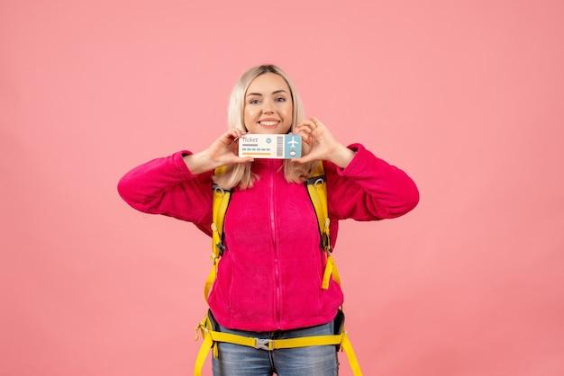 Вид спереди улыбающаяся женщина-путешественница в повседневной одежде в рюкзаке с билетом