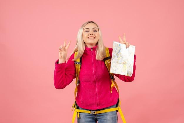 Вид спереди улыбающаяся женщина-путешественница с желтым рюкзаком, держащая карту, жестикулирующую знак победы