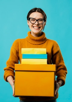Front view of smiling woman carrying boxes
