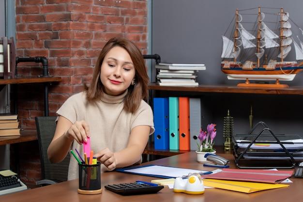 Вид спереди улыбающаяся женщина, принимающая маркер, сидя у стены