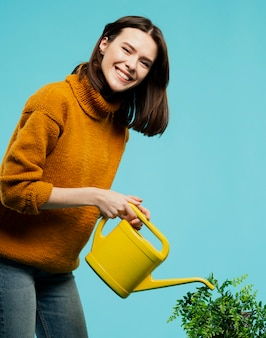 Front view of smiling woman with watering can