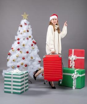 クリスマスツリーとプレゼントの近くに彼女の旅行バッグを保持しているサンタの帽子と笑顔のクリスマスの女の子の正面図