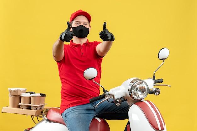 Vista frontale del giovane adulto sorridente che indossa la camicetta rossa e guanti del cappello nella mascherina medica che consegna l'ordine che si siede sullo scooter che fa il gesto giusto su fondo giallo