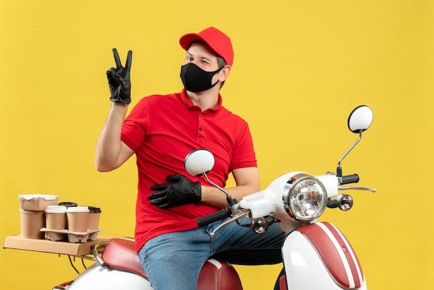 Vista frontale del giovane adulto sorridente che indossa la camicetta rossa e guanti del cappello nella mascherina medica che consegna l'ordine che si siede sullo scooter che fa il gesto di vittoria su fondo giallo