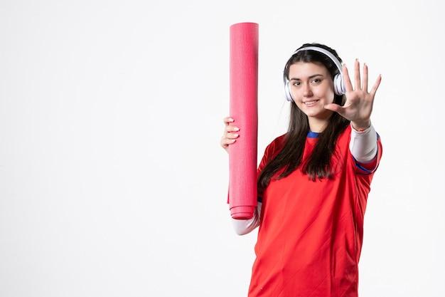 Вид спереди улыбающаяся молодая женщина в спортивной одежде, держащая коврик для йоги