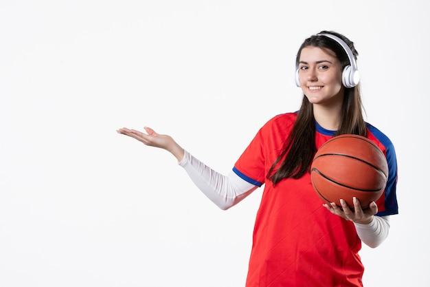 Вид спереди улыбающаяся молодая женщина в спортивной одежде с баскетболом
