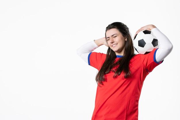 Вид спереди улыбающаяся молодая женщина в спортивной одежде с футбольным мячом