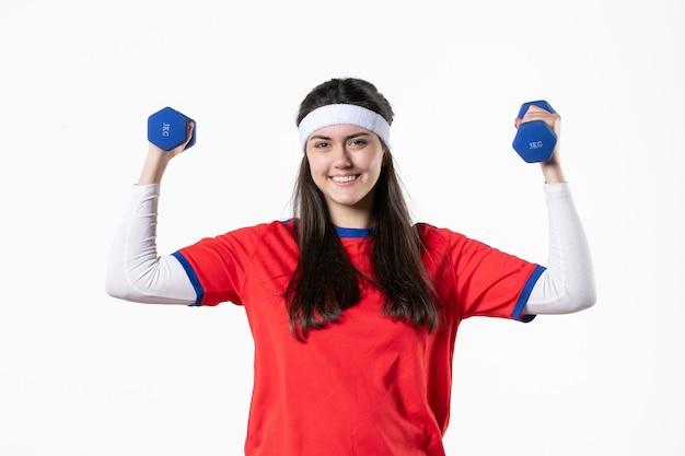 ダンベルでワークアウトスポーツ服を着て若い女性の笑顔の正面図