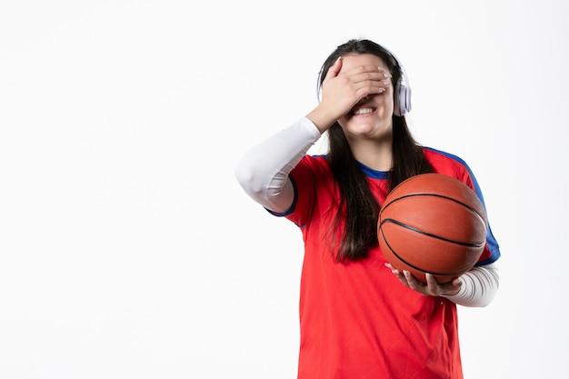 Vista frontale sorridente giovane femmina in abiti sportivi con basket