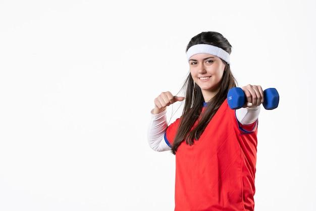 Vista frontale sorridente giovane femmina in abiti sportivi con manubri blu