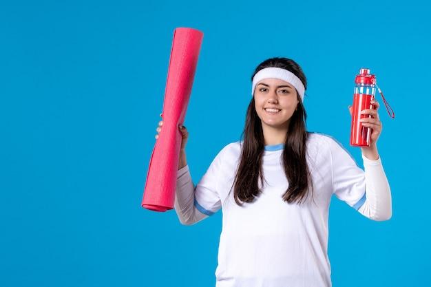 Вид спереди улыбающаяся молодая женщина с ковриком для йоги