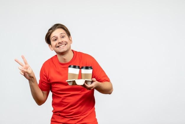 Vista frontale del giovane ragazzo sorridente in camicetta rossa che tiene il caffè in bicchieri di carta e che fa gesto di vittoria su priorità bassa bianca
