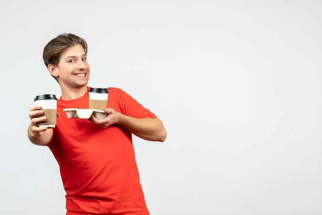 Vista frontale del giovane ragazzo sorridente in camicetta rossa che tiene il caffè in bicchieri di carta su sfondo bianco
