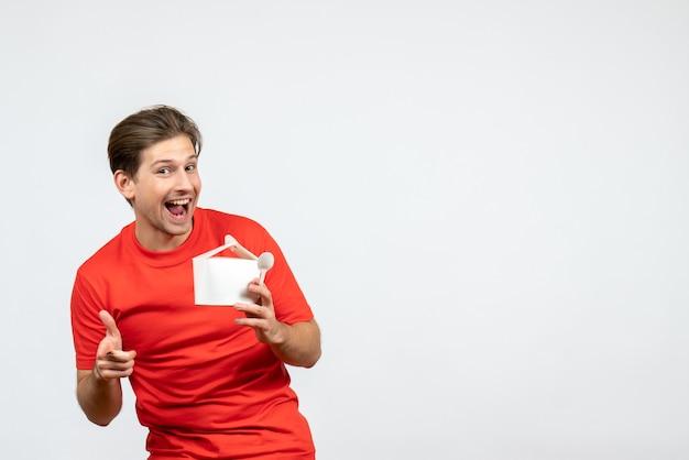 Vista frontale del giovane ragazzo sorridente in camicetta rossa che tiene la scatola di carta e il cucchiaio che punta in avanti su sfondo bianco