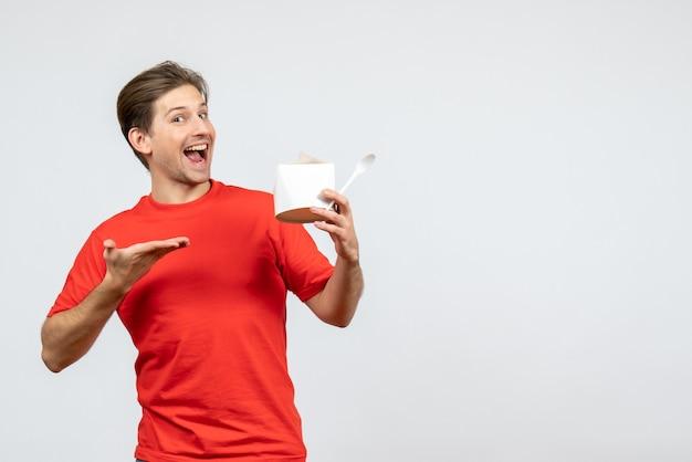 Vista frontale del giovane ragazzo sorridente in camicetta rossa che indica la scatola di carta su priorità bassa bianca