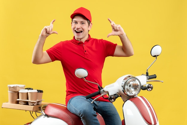 Front view of smiling young guy wearing red blouse and hat delivering orders making exact something on yellow background
