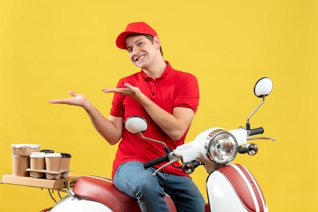 Vista frontale del giovane ragazzo sorridente che indossa la camicetta rossa e il cappello che trasporta gli ordini che indicano qualcosa sul lato destro su sfondo giallo