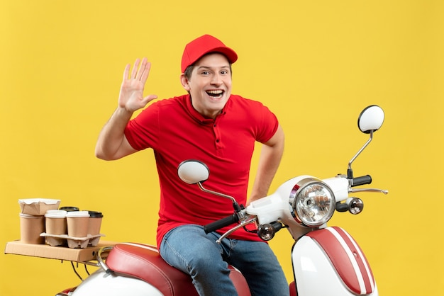 Vista frontale del giovane ragazzo sorridente che indossa la camicetta rossa e il cappello che trasporta gli ordini che mostrano dieci su fondo giallo