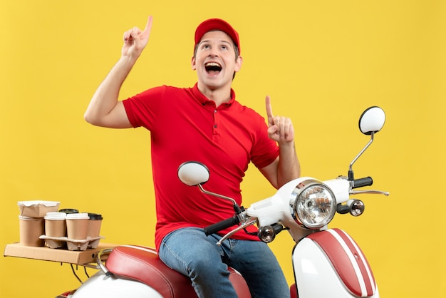 Vista frontale del giovane ragazzo sorridente che indossa la camicetta rossa e il cappello che trasporta gli ordini che mostrano su fondo giallo