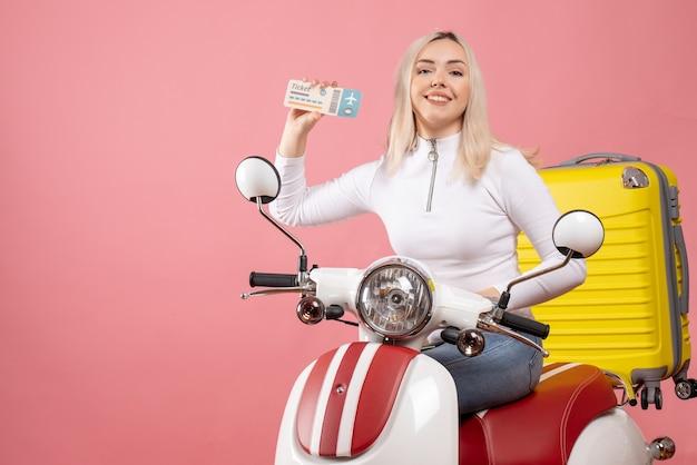 Вид спереди улыбающаяся молодая леди на мопеде, показывающая билет