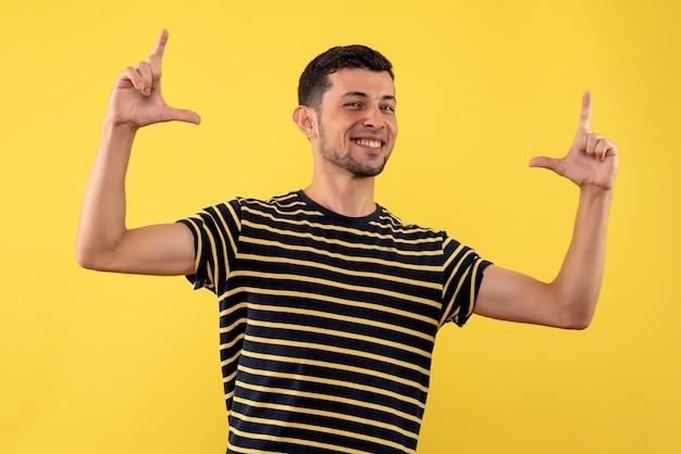 Вид спереди улыбающегося молодого человека в черно-белой полосатой футболке, стоящего на желтом изолированном фоне