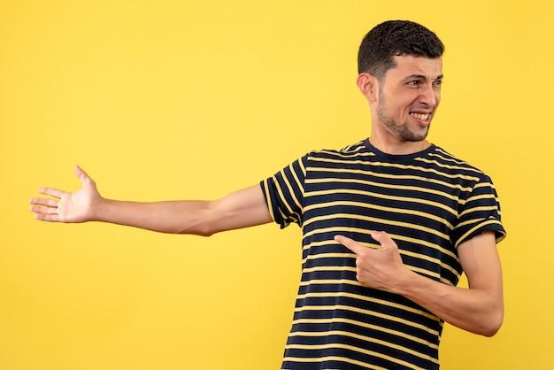 Вид спереди улыбающегося молодого человека в черно-белой полосатой футболке на желтом изолированном фоне
