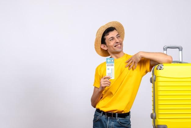 Вид спереди улыбающегося молодого человека в желтой футболке, стоящего возле желтого чемодана с билетом