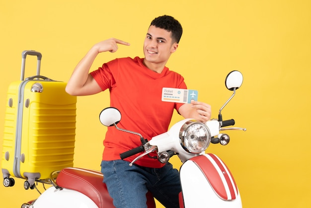 Front view smiling young man on moped holding ticket on yellow background